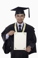 Man in graduation robe holding a blank certificate