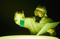 Man in protective suit inspecting a bottle of chemical