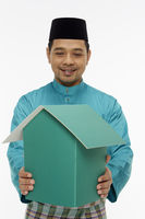 Man in traditional clothing holding up a cardboard house