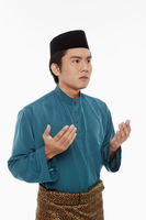 Man in traditional clothing lifting up hands, praying
