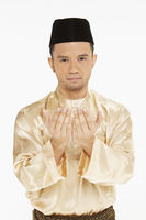 Man in traditional clothing lifting up his hands, praying