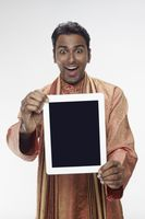 Man in traditional clothing showing digital tablet