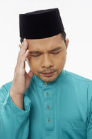 Man in traditional clothing touching his forehead