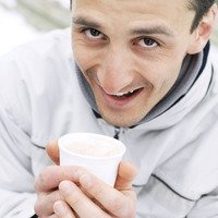 Man in warm clothing holding a cup of hot drink