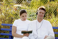 Man listening to music on the headphones while his wife is reading book