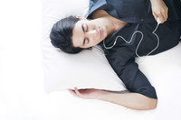Man listening to music on the mp3 player while lying on the bed