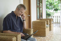 Man on patio using cell phone and laptop