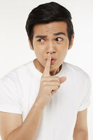 Man placing finger on lips