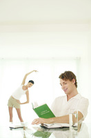 Man reading book while his girlfriend is exercising in the background