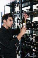 Man selecting wine bottle from rack