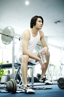Man sitting in gym holding bottled water