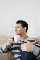 Man sitting on the couch enjoying a cup of coffee