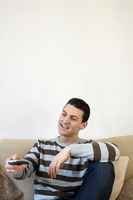 Man sitting on the couch holding television remote control