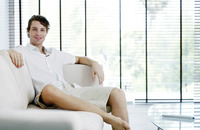 Man sitting on the couch smiling at the camera
