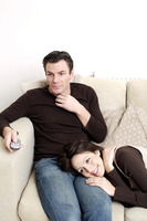 Man sitting on the couch with his wife lying on his lap