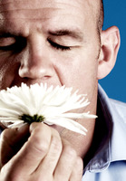 Man smelling a white flower