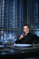 Man smiling while holding a glass of wine