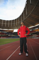 Man standing on running track and looking away