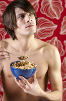 Man thinking while eating a bowl of breakfast cereal