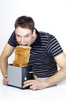 Man trying to eat a stack of toasts