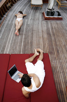 Man using laptop while his girlfriend is sunbathing