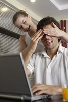 Man using laptop, woman covering man's eyes from behind