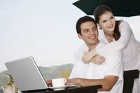 Man using laptop, woman hugging man from behind