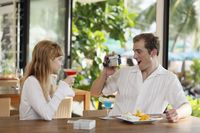 Man using video camera to record woman holding cocktail drink