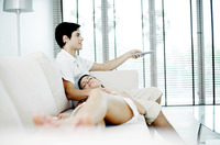 Man watching television with his girlfriend lying on his lap