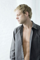 Man with unbuttoned shirt thinking
