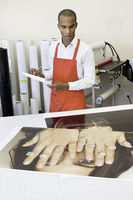 Man working at printing press with photo printouts on table
