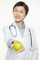 Medical personnel holding a green apple
