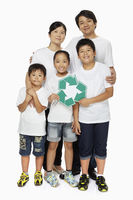 One happy family holding up a recycle logo