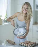 Portrait of woman mixing cookie batter in kitchen at counter