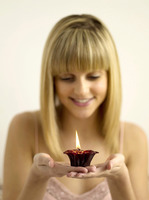 Pretty girl holding a lighted aromatherapy candle