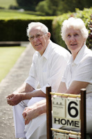 Senior couple sitting on a bench in a bowling green