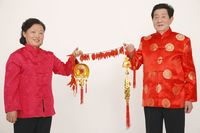Senior man and woman holding chinese decorations