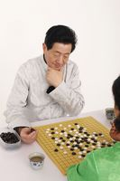 Senior man and woman playing japanese board game