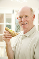 Senior man smiling at the camera while holding sandwich