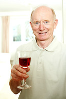 Senior man smiling while holding a glass of red wine