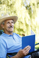Senior man with hat holding a book