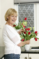 Senior woman arranging flowers at home
