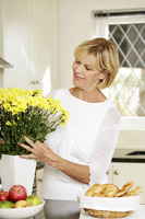 Senior woman arranging flowers in a vase