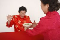 Senior woman serving a bowl of noodles to senior man