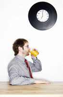 Side shot of a bespectacled man drinking a glass of orange juice for his breakfast