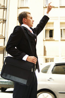 Side shot of a man in business suit with a sling bag stopping a taxi