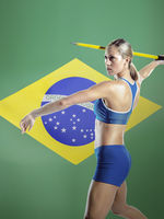 Side view of female athlete throwing javelin against brazilian flag