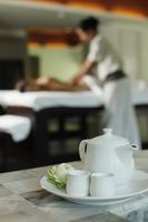 Teapot and tea cups, woman receiving massage on the background