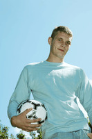 Teenage boy posing with a soccer ball on the field