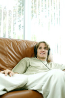 Teenage boy sitting on the couch listening to music on the headphones